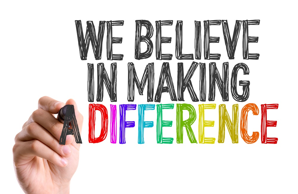 Hand with marker writing We Believe in Making a Difference